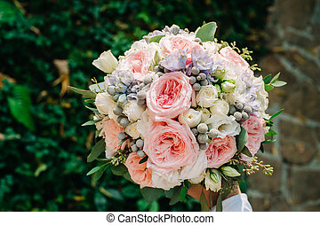 Beautifully decorated bouquet closeup with white and pink roses, sky flowers