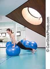 Young woman with pilates ball in the gym