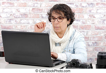 portrait of middle-aged woman using laptop