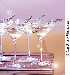 Glasses of with white champagne decorated with lavender on...