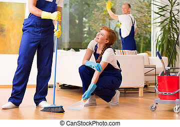 Co-workers during cleaning - Co-workers with broom during...