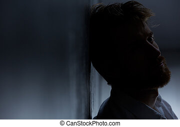 Young man suffering from depression, sitting alone in dark...