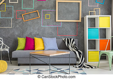 Concrete wall with colored frames in modern cozy living room