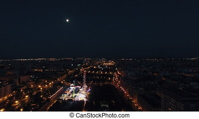 Aerial night view of lighted ferris wheel in amusement park...