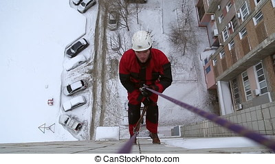 Industrial climber climbs down from the roof of a high-rise...