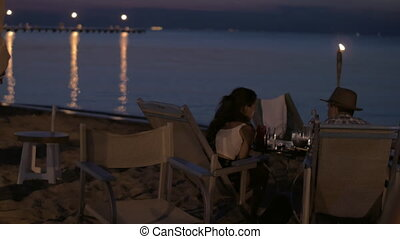 View of young happy couple having romantic dinner on the...