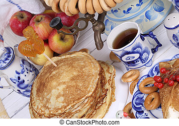 Pancakes are stacked on a plate on a festive table -...