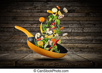 Fresh vegetables flying into a pan