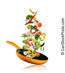 Fresh vegetables flying into a pan on white background