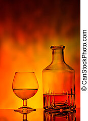Glass and decanter of cognac on fire background