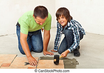 Boy helping his father placing a ceramic floor tile -...