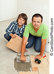 Father and son mounting ceramic floor tiles together in a...