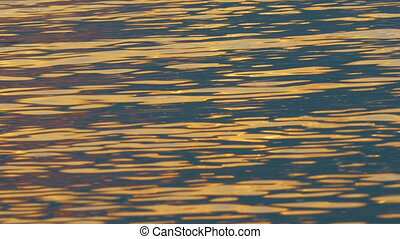 Water sparkling with evening sun light - Close-up shot of...