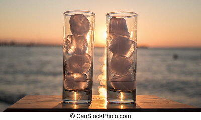 Glasses with melting ice against sea and sunset background