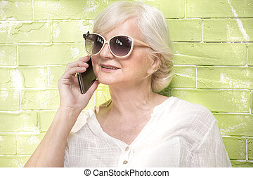 Senior woman talking by mobile phone. - Portrait of...