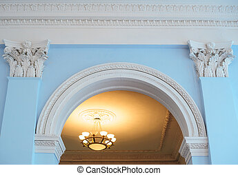 white arch on a blue wall inside the building and two...