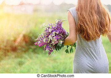 woman with a bouquet of lupine flowers on a sunny summer...