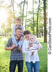 Young parents with children walk in the summer park