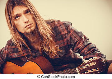 Sitting man playing guitar. - Sitting long haired bearded...