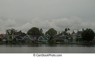 Timelapse of clouds over houses on river bank, Netherlands -...