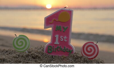 One year old birthday candle on the beach - Close-up shot of...