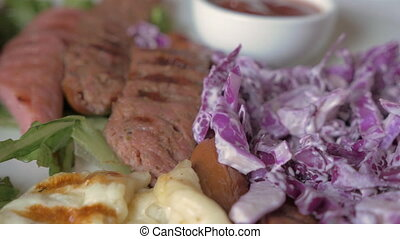 Eating sausages and red cabbage salad