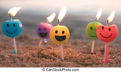 Smiley candles on the beach - Close-up shot of burning...