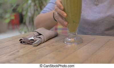Drinking mint smoothie in cafe - Woman taking a glass with...