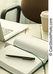 Open notepad with black pen on work-table. Paper cup of...