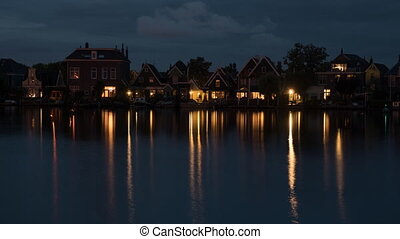 Timelapse of night coming to waterside village in...