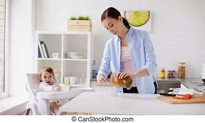 mother cooking food and feeding baby at home - family, food,...