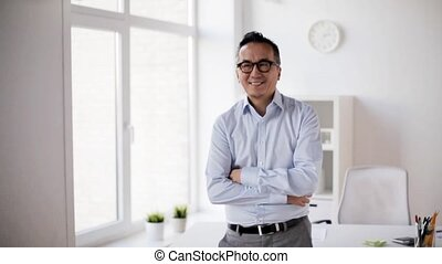 happy asian businessman waving hand at office - business,...