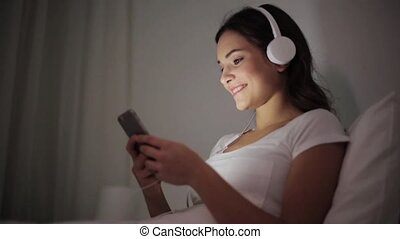 woman with smartphone and headphones in bed - technology,...