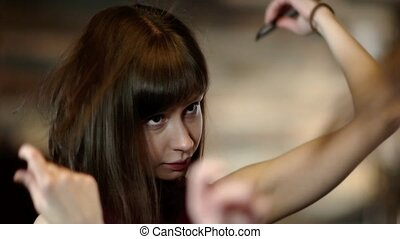 Young woman looking in the mirror brushing her hair