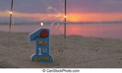 One year old baby boy birthday candle on the beach -...