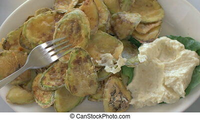 Fried zucchini with cream sauce - Close-up shot of a woman...