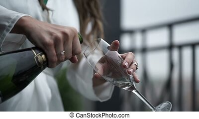 Young woman opens bottle of champagne - Young woman in white...