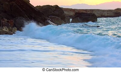 beautiful sunset on wavy beach with waves breaking in cliffs