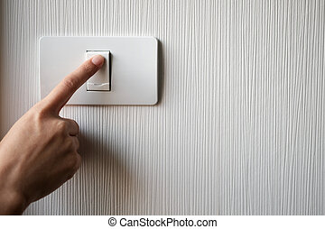 Turning on or off on light switch - Close up of finger is...