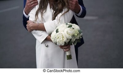 Young couple embracing on a street with bouquet
