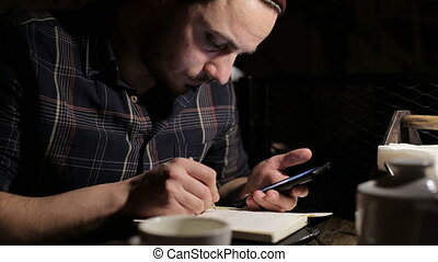 Young Man writing a to do list in a bar at night