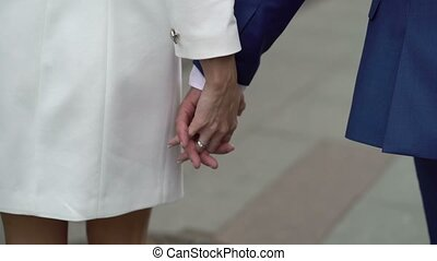 Young lovely couple holding hands and walking on a street