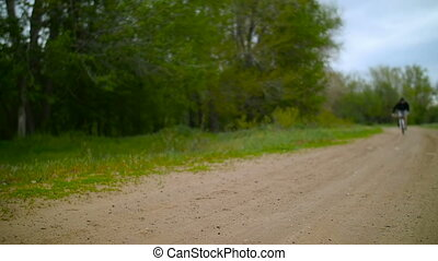 Cyclist Rides On A Bike On The Dirt Road