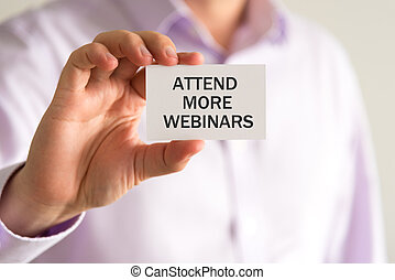 Businessman holding a card with text ATTEND MORE WEBINARS -...
