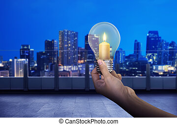 Hand holding light bulb with shining candle inside it on...