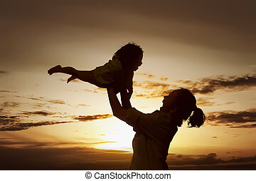 Mother Day Concept - Happy woman playing with little girl on...
