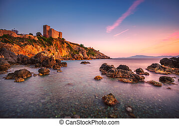 Talamone rock beach and medieval fortress at sunset. Maremma...