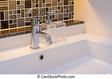 washbasin with faucet and liquid soap bottle at home