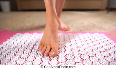 Female feet gently tread on acupuncture massage mat. Close...