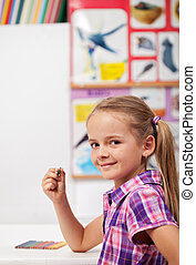 Little girl at the school sitting in the front desk - turning back